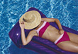 Woman Floating In Water - Straw Hat Over Her Face stock photo
