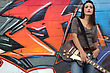 Woman With Guitar In Front Of Graffiti stock photography
