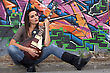 Woman With Guitar In Front Of Painted Wall stock photography