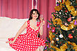 Woman Pin-up Sits Near Fir-tree With Wineglass stock image