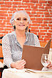 Seniors Woman Reading A Menu In A Restaurant stock photo