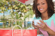 Woman With A Shopping Bag Drinking Tea Outside
