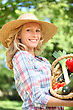 Woman Smiling With A Straw Hat Holding Basket Of Vegetables stock photography
