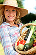 Woman With A Straw Hat Holding Basket Of Vegetables. stock photo