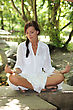 Yoga Woman In White Sitting Cross Legged In The Park stock photography