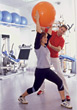 Women Exercising With Swiss Ball & Personal Trainer