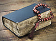 Wooden Rosary And The Bible On The Table stock photo