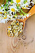 Wooden Spoon With Dried Chamomile Flowers, A Bouquet Of Fresh Chamomile Flowers On A Background Of Wooden Boards stock photo