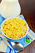 Yellow Corn Flakes With Milk In A Jug, Spoon, Napkin Against A Wooden Board stock photography