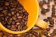 Yellow Cup With Many Coffee Beans On The Table stock image