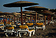 Yellow Sunbeds And Wooden Umbrellas At Sandy Beach Lit By Late Afternoon Sun stock photography