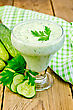 Yogurt In Glass With Cucumber, Parsley, Napkin Against A Wooden Board stock photo