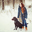 Outing Young Beautiful Female Walking With Labrador Dog In Snowy Winter Forest. Woman Looking At Camera And Holding Dog. Selective Focus stock image