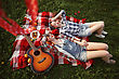 Young Beautiful Smiling Girls Dressed In Pin Up Style Lying And Dreaming On A Red Plaid On Green Grass In Summer Park. Aerial View