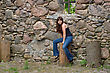 Young Beautiful Woman Sitting On The Log Near Old Castle Ruins
