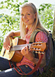 Young Blonde Woman Playing Guitar stock image