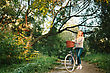 Young Blonde Woman On A Vintage Bicycle In The Park. Hipster Style stock photo