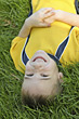 A young boy laying in the grass upside down stock photo