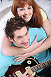 Young Couple At Home With A Guitar stock photography
