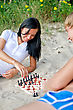 Young Couple Playing Chess On The Beach stock image