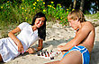 Young Couple Playing Chess On The Beach stock photography