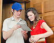 Young Courier Deliver Package To Pretty Woman stock image