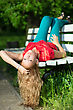 Young Curly Blond Woman Lying On The Bench