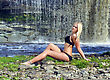 Young Girl In Black Bikini Sitting On A Waterfall Background