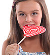 Young Girl Eating A Heart Shaped Lolly stock photo