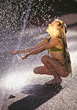 Young Girl Playing With Water Sprinkler stock photo