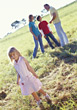 Young Girl Standing In Fields, Family In Background stock photography