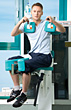 Young Man Performing Gym Machine Exercise stock photo