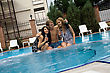 Young Man And Two Girls Drink Champagne In Pool stock photo