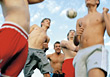 Young Men In Beach Shorts Practicing Volleyball stock photography