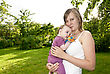 Young Mother In The Garden With A Baby At Summer Day stock photo