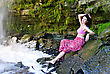 Young Pretty Girl Sitting On A Rock Near Waterfall