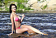 Young Pretty Girl Sitting On A Rock On The River Shore