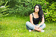 Young Thoughtful Brunette Sitting In The Grass Near Bushes stock photo
