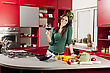 Young woman with glass of red wine in the kitchen stock photography