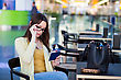 Young Woman With Glasses Sitting In The Airport Waiting Room And Reading Her Tickets stock photo