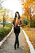 Young Woman Is Walking Outdoors In Autumn Alley