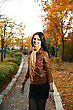 Young Woman Is Walking Outdoors In Autumn Alley stock photo