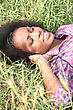 African-American Young Woman Lying On The Grass stock image