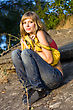 Young Woman Sitting On The Stones With Yellow Bag stock photo