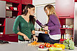 Young women preparing meal in the kitchen stock photography