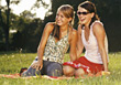 Young Women Sitting in Park Laughing stock photography